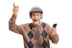El escuchar mayor alegre la música en un teléfono imagenes de archivo
