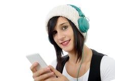 El escuchar moreno joven la música con los auriculares y el teléfono Foto de archivo libre de regalías