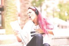 El escuchar muy emocionado joven de la mujer la música en la tableta en foto de archivo
