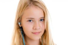 El escuchar rubio agradable de la muchacha misic fotografía de archivo