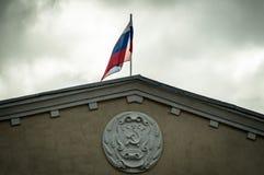El escudo de armas del RSFSR y la bandera rusa en el edificio administrativo en la región de Kaluga en Rusia Imagen de archivo libre de regalías