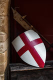 El escudo medieval y el arma de la bandera de Inglaterra que descansan sobre la pared echan a un lado Foto de archivo libre de regalías