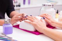 El esmalte de uñas de la mujer del salón de los clavos quita con el tejido Fotos de archivo libres de regalías