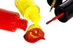 El esmalte de uñas rojo y amarillo es descensos abiertos, mezclados y derramados Foto de archivo