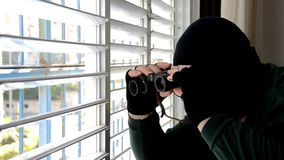 El espía en máscara del pasamontañas está mirando a través de las persianas del obturador almacen de video