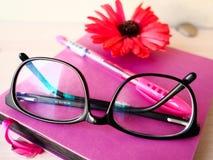 El espacio de ejecución de los vidrios del cuaderno de las mujeres de negocios encierra la flor Fotos de archivo libres de regalías