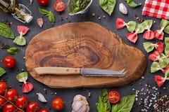 El espacio de la copia en la madera cortó al tablero con el cuchillo del queso Farfalle, tomates de cereza, ajo, albahaca, pesto, fotos de archivo libres de regalías