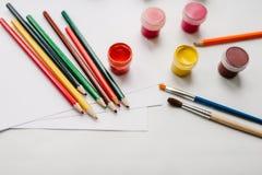 El espacio de trabajo del artista para dibujar Lápices coloreados, acuarela, pinturas, cepillo, sketchbook, Libro Blanco aislado  fotos de archivo libres de regalías