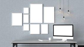 El espacio de trabajo moderno con los marcos vacíos aislados en la pared de ladrillo y es Foto de archivo