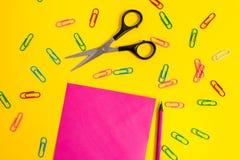 El espacio en blanco coloreó los clips de papel de la hoja dibuja a lápiz el fondo del color claro de las tijeras Acontecimientos imágenes de archivo libres de regalías
