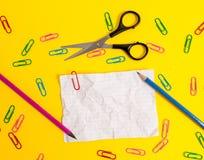 El espacio en blanco coloreó los clips de papel machacados de la hoja dibujó a lápiz el fondo ligero de las tijeras Acontecimient imagen de archivo libre de regalías