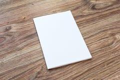 El espacio en blanco del folleto está en un escritorio de madera Imagen de archivo
