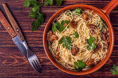 El espagueti de las pastas con los mízcalos prolifera rápidamente en fondo de madera Imagenes de archivo