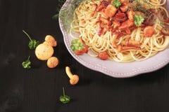 El espagueti italiano con los mízcalos prolifera rápidamente en un b de madera oscuro fotografía de archivo libre de regalías