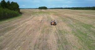 El esparcidor del fertilizante se mueve a la cámara a lo largo del campo cosechado almacen de metraje de vídeo