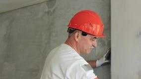 El especialista alinea la pared en el cuarto Reparaciones en la casa almacen de metraje de vídeo