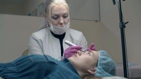 El especialista de la cosmetología que habla aplica maquillaje permanente almacen de video