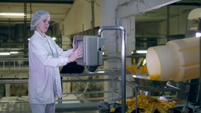 El especialista de la señora está regulando una máquina microprocesador-que produce almacen de video