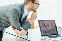 El especialista de las finanzas mira la pantalla del ordenador portátil con las cartas financieras el desarrollo del ` s de la co foto de archivo