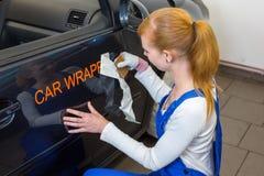 El especialista de marcado en caliente del coche pone el logotipo con el coche que envuelve la película en el automóvil fotos de archivo libres de regalías