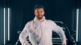 El especialista de sexo masculino del mantenimiento del coche está celebrando un buffwheel y una sonrisa almacen de metraje de vídeo