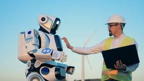 El especialista de sexo masculino está regulando los ajustes del robot en su panel táctil almacen de metraje de vídeo