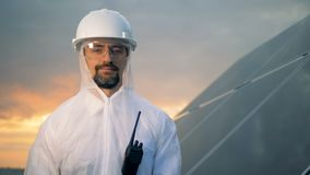 El especialista de sexo masculino sonriente en desgaste de la protección se está colocando cerca de una construcción solar metrajes