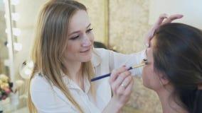 El especialista del maquillaje aplica un lápiz corrector al párpado superior del cliente usando un cepillo Primer de una morenita almacen de video