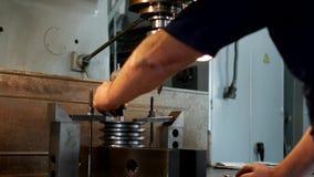 El especialista del varón mide el tamaño del dispositivo de la tolerancia y el valor en la polea del metal para fabricar, cercana almacen de video