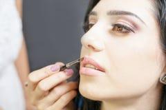 El especialista en salón de belleza consigue el lápiz labial, lustre del labio, maquillaje profesional Imagenes de archivo
