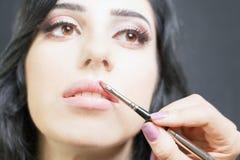 El especialista en salón de belleza consigue el lápiz labial, lustre del labio, maquillaje profesional Foto de archivo