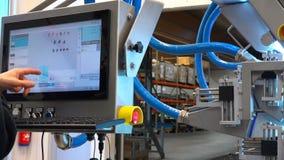 El especialista hace ajustes a la exhibición ambarina de la máquina almacen de video