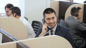 El especialista joven está hablando en el teléfono mientras que se sienta en compañía prometedora metrajes