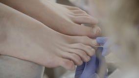 El especialista joven limpia el clavo del pie del cliente que usa el palillo del metal en salón almacen de metraje de vídeo