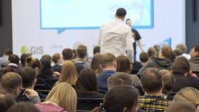 El espectador o el visitante en un seminario hace a altavoz una pregunta almacen de metraje de vídeo