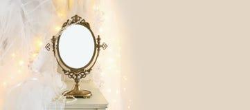 El espejo oval del viejo vintage y el vestido y el velo blancos hermosos de boda en silla con la guirnalda del oro se enciende imagen de archivo