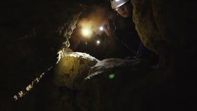 El espeleólogo encuentra el paso peligroso en la cueva almacen de metraje de vídeo