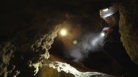 El espeleólogo encuentra el paso peligroso en la cueva y comienza a ir 4K metrajes