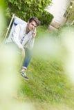 El esperar adulto joven en el teléfono que se sienta en el jardín Fotos de archivo