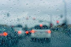 El esperar en un empalme del tráfico la luz verde durante un día lluvioso; fotografía de archivo