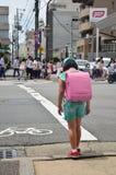 El esperar japonés de la muchacha de los niños cruza encima el camino Imágenes de archivo libres de regalías
