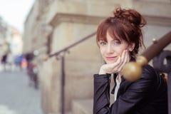 El esperar que se sienta sonriente de la mujer en una calle urbana Imágenes de archivo libres de regalías