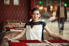 El esperar solo hermoso de la mujer joven en una tabla en restaurante Foto de archivo