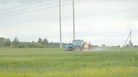 El espray del tractor fertiliza el campo con las sustancias químicas almacen de metraje de vídeo