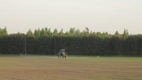 El espray del tractor fertiliza en campo con las sustancias químicas en campo de la agricultura almacen de video