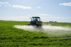 El espray del tractor fertiliza la sustancia química del pesticida del campo Fotos de archivo