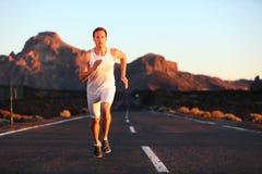 El esprintar de funcionamiento del atleta en la puesta del sol en el camino Imagenes de archivo
