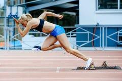 el esprinter explosivo del atleta de sexo femenino del comienzo funciona con 200 metros Fotos de archivo libres de regalías