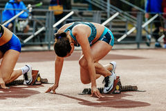 el esprinter listo del atleta de sexo femenino del comienzo funciona con 100 metros Imágenes de archivo libres de regalías