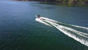 El esquí acuático de la persona ató al barco de motor en paisaje marino tropical del horizonte de la montaña del océano en la opi almacen de video